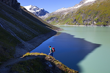 A male hiker on the border of shadow and sunlight, high above the Mooserboden lake, during the Glocknerrunde, a 7 stage trekking from Kaprun to Kals around the Grossglockner, the highest mountain of Austria.
