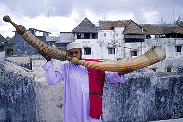 Swahili man blowing the ivory Pate Siwa, a horn carved from an elephant tusk (ivory). On a rooftop in Lamu town on Lamu, an island in the Indian Ocean off the northern coast of Kenya