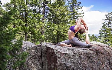 Flexible female practices yoga outside