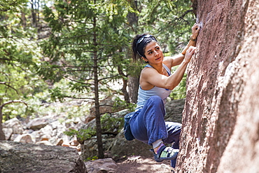 Strong female looking towards next move on a boulder problem