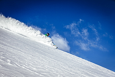A man skiing fresh snow on a sunny day. Alta, Utah