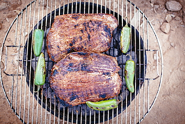 Steak and pepers cookin on a grill.