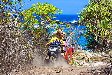 Two surfers travelling by bike.Sumbawa island.Indonesia.