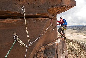 A man rock climbing a desert sandstone tower called Psycho Babble Tower in the Big Gypsum Valley near, Naturita, Colorado.