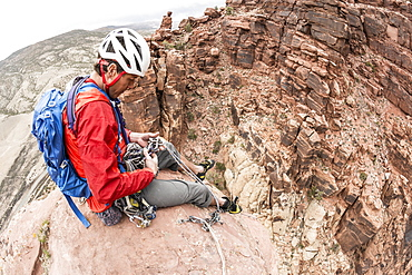 A man preparing to descend a desert sandstone tower called Psycho Babble Tower in the Big Gypsum Valley near, Naturita, Colorado.