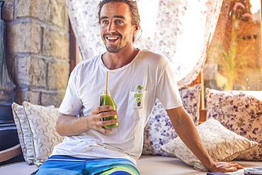 Young man is drinking juice, Kuta, Bali, Indonesia