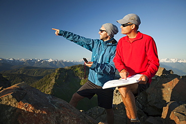 Two men use a paper map and a compass to identify nearby peaks while hiking in the North Cascade Mountain Range, North Cascades National Park, Washington, United States of America