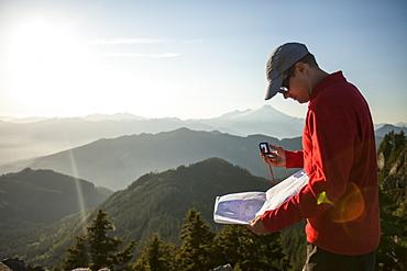 A man uses a compass and paper map to navigate while hiking in the North Cascade Mountain Range, North Cascades National Park, Washington, United States of America