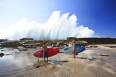Pro SUP athletes Iballa Ruano and Vilayta watch the waves breaking against a pier in the Canary Islands.