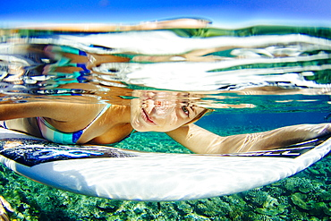 Underwater portrait of professional surfer Lucia Martiño with her surfboard
