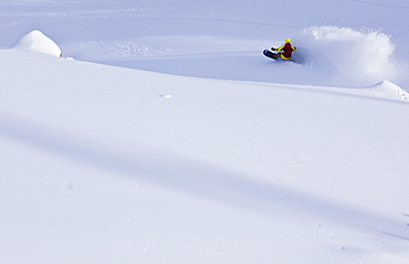 A man slashes deep snow on his snowboard and creates a large powder cloud in Utah's Wasatch mountains.
