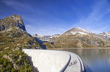 Four road bikers on the dam of the Emosson reservoir lake in the Alps on the border of France and Switzerland. It is an early morning training session of the local cyclists. The climb from Martigny to Finhaut will be stage 17 of the 2016 Tour de France on July 20th 2016. Depart is in Bern and the finish near the Emosson reservoir, Lac d'Emosson, at 1960 meters height.