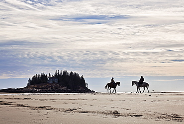 Two people ride horses down a sandy Maine beach.