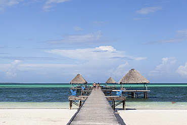 Couple walking on a wooden jetty on a the pristine tropical beach in Cayo Guillermo. Cuba