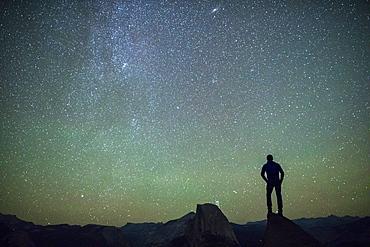 Man standing on a rock looking at Half Dome at night. Yosemite, CA, USA.
