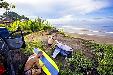 Young surfers are waxing their boards before surf session, Balian village, Bali, Indonesia