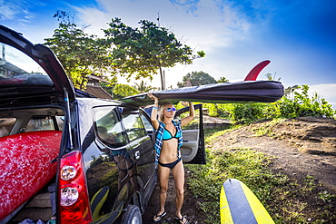 Young woman with surfboard, Balian village, Bali, Indonesia