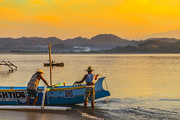 Indonesian men with a boat at sunrise time, Gerpuk, Lombok, Indonesia