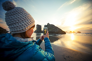 A young woman uses her smartphone to take a picture of the sunset from Bandon Beach, Oregon, United States of America