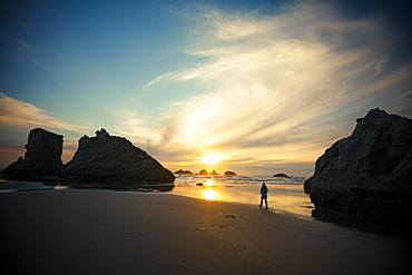 A young woman walks along Bandon Beach, Oregon, United States of America