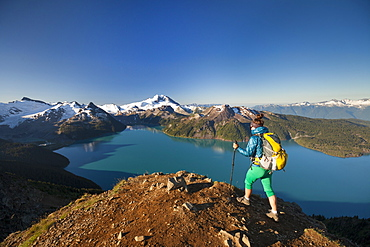 A backpacker reaches the summit of Panorama Ridge, overlooking Garibaldi Lake in Garibaldi Provincial Park, British Columbia, Canada.