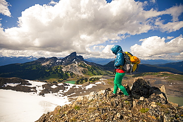 A young woman hiking on Panorama Ridge with Black Tusk Mountain in the background in Garibaldi Provincial Park, British Columbia, Canada.