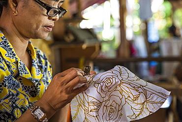 An Indonesian woman paints batik by hand in Ubud, Bali