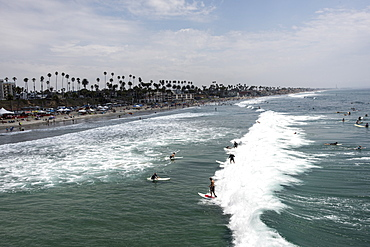 """Surfers catch a """"party wave"""" after taking part in a paddle out honoring local surfing legend known as Skydog at Oceanside Beach in Oceanside, Calif., on August 3, 2014."""