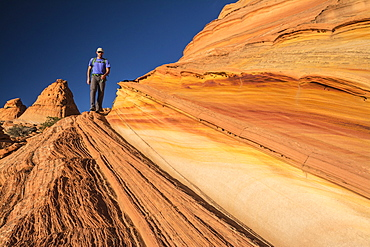 A man hiking along sandstone layers, South Coyote Buttes, Vermillion Cliffs National Monument, Kanab, Utah.