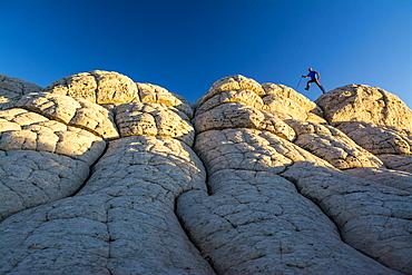 A man hiking along sandstone layers, White Pocket, Vermillion Cliffs National Monument, Kanab, Utah.
