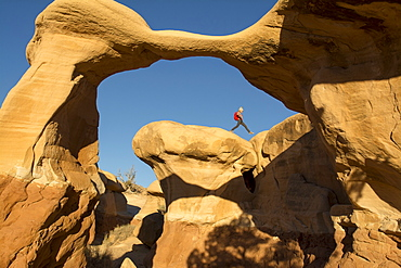 A young girl hiking along the edge of Metate Arch in the  Devil's Garden, Hole in the Rock Road, Grand Staircase-Escalante National Monument, Escalante, Utah.