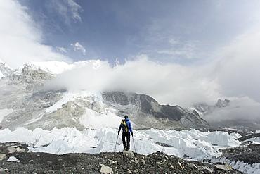 A trekker stands over the Khumbu Glacier in Everest Base Camp.