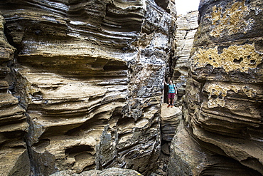 A young man stands in the bottom of a narrow, deep slot canyon looking up at the striated rock walls.