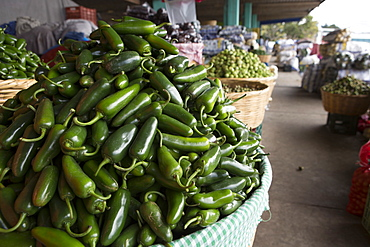 A closeup view of a basket of green chili peppers.