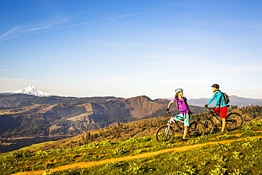 Two young women stop to rest on mountain bikes while riding a single-track trail through an open meadow with river and volcano in distance.