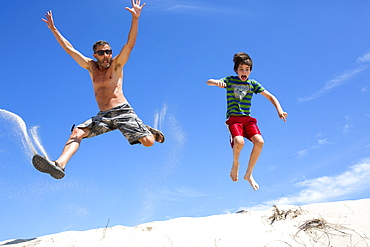 A man and boy jump on a sand dune in Provincetown, MA.