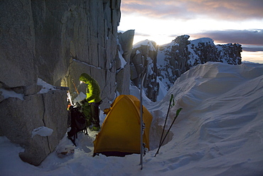 A man camped on the summit ridge after  climbing Thunderbolt Ridge in Hogum Fork while on a backcountry ski tour in Little Cottonwood Canyon, Lone Peak Wilderness, Uinta-Wasatch-Cache National Forest, Salt Lake City, Utah.