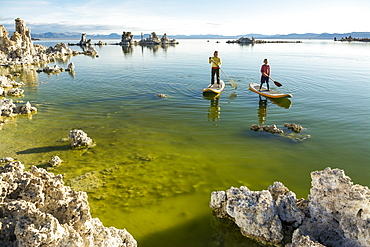 A woman and her daughter stand up paddleboarding on Mono Lake from South Tufa Beach, Lee Vining, California.