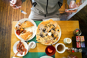 Man sitting in front of breakfast food at a restaurant, using smartphone