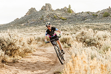 Person Mountain Biking On Trail In Desert Landscape