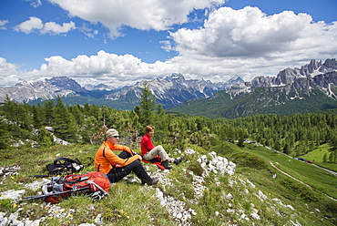 A Couple Taking Rest At The Cinque Torri Area In The Dolomites, Italy