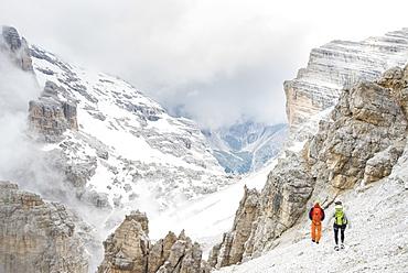 A Couple Hiking Down The Summit Of Punta Anna In Tofana Di Mezzo