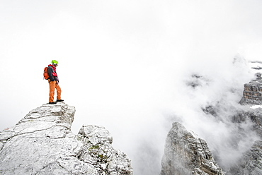 The Italian Guide Standing On Exposed Ridge Near The Summit Of Punta Anna