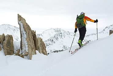 A man passing granite spires on a backcountry ski tour in Little Cottonwood Canyon