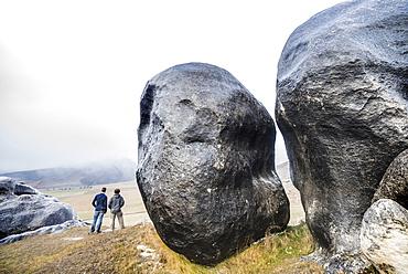 Two Men Exploring Castle Hill Near Arthur's Pass Outside Of Christchurch, New Zealand