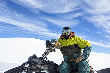 Portrait of a man sitting on snowmobile in Northern British Columbia