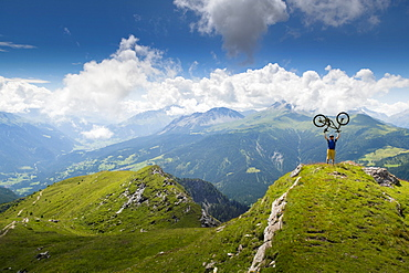 Distant View Of Mountain Bike On Summit Of Mountain Lifting Mountain Bike Above His Head