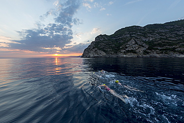 A Group Of Swimmers Swimming In The Mediterranean Sea At Sunset