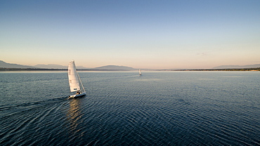 Two Sailboats Gently Gliding Across The Lake