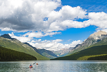 Two Kayakers Kayaking On Bowman Lake In Glacier National Park